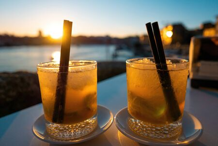 Two beverages cocktails at sunset with straws