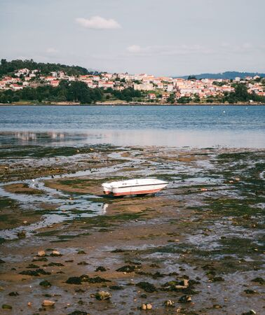 Old wooden boat in low tide with moss in Combarro, northern Spain