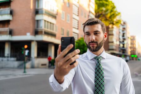 Young business man with white shirt and tie in outdoor city looking at smartphone