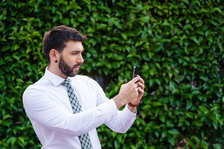 Young business man with white shirt and tie in outdoor park taking a photo with phone