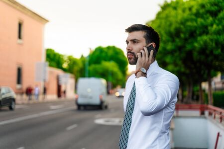 Young business man with white shirt and tie in outdoor city making a phone call
