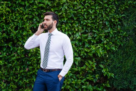 Young business man with white shirt and tie in outdoor park making phone call