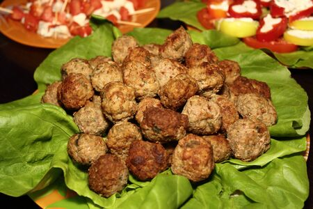 meatballs and green salad set on a plate photo