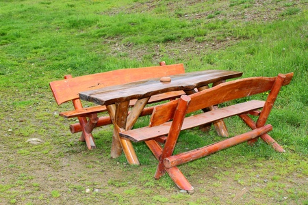 outdoor wooden bench near a lodge in the mountains photo