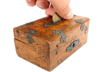 wooden insert: putting a romanian coin in very old moneybox Stock Photo