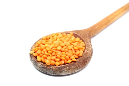 bunch of red lentil in old spoon over white