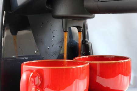 making espresso coffee in two red cups