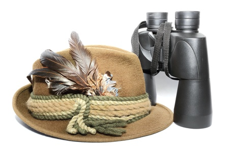 display of a hunting hat and binoculars over white