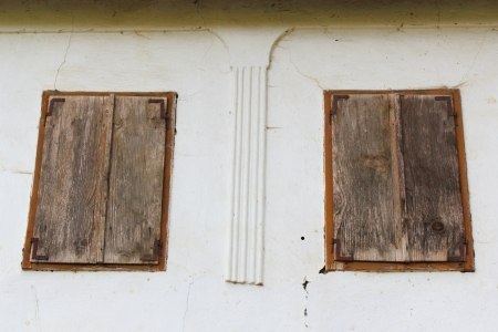 windows with wooden blinds closed, abandoned old house in Rimetea, Romania photo