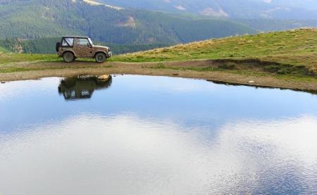Vehículo para terrenos extremos cerca del lago Icoana, montañas Suhard, Rumania Foto de archivo - 15644531