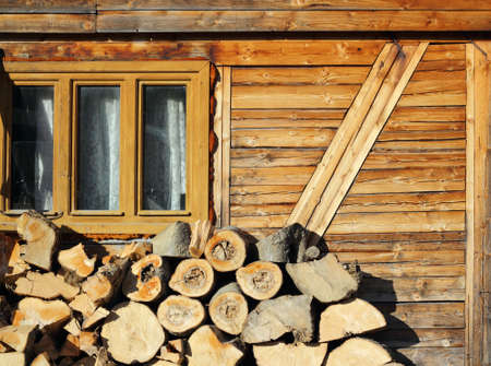 wood prepared for the fireplace near an old lodge up in the mountains photo