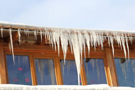 long big icicles on a house roof in a cold winter day photo