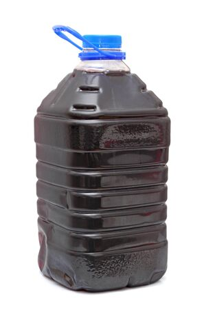 homemade red wine in plastic container with blue cap over white background photo