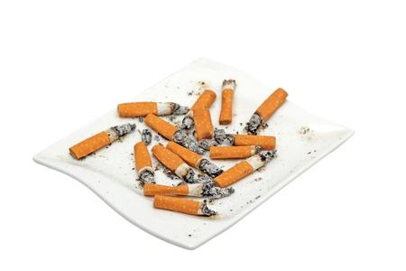 transformed: cigarrillos en un plato transformado en el cenicero Foto de archivo