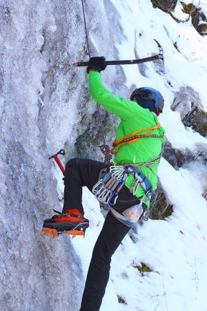ax man: man in green jacket climbing an ice wall - motion blur on ice ax