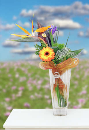 colorful floral arrangement in a vase on a white table - meadow with flowers in the background photo