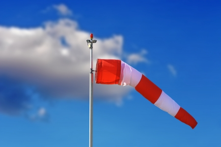 空港での青い空の上の赤と白の吹流し