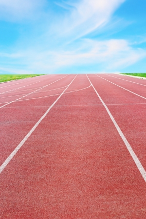 dross: detail of a running track towards the horizon and blue sky Stock Photo