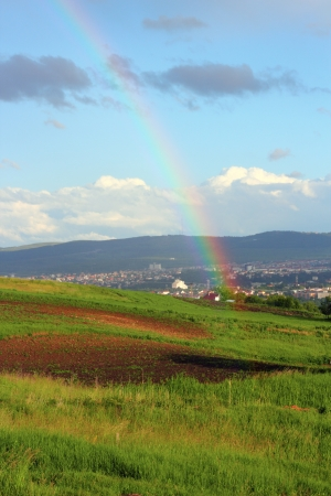 beautiful rainbow photographed from the hills near the city photo