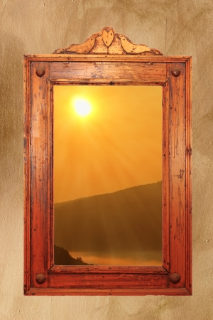 beautiful colors of sunrise seen through a window with old wooden frame photo