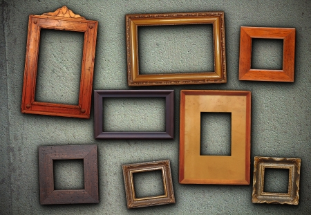 lots of empty picture frames hung on green wall ready for your design photo