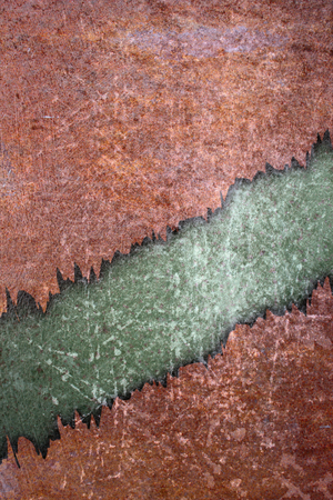cracked rusty backdrop with green and orange scratched surfaces photo