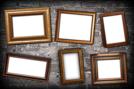 messy arrangement of wooden frames over grungy brick wall with place for text or message on white paper photo