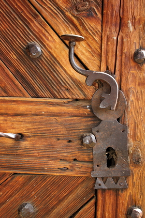 ancient latch on beautiful wooden door, entrance detail of old romanian traditional church photo
