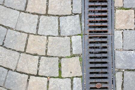 drainage on pedestrian street, textured background Standard-Bild