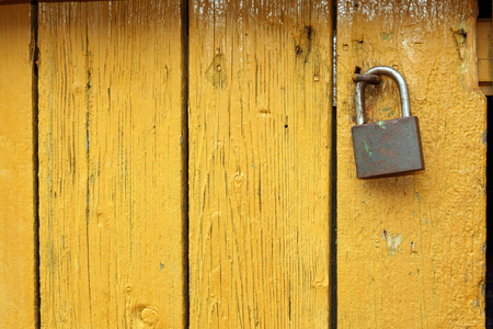 old metallic padlock on yellow wooden door, interesting textured view photo