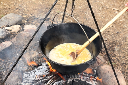 cooking in a black cauldron on camping fire, slow food Standard-Bild
