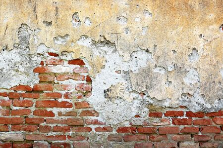 cracked plaster layer on brick wall, effects of dampness from the soil on old building masonry