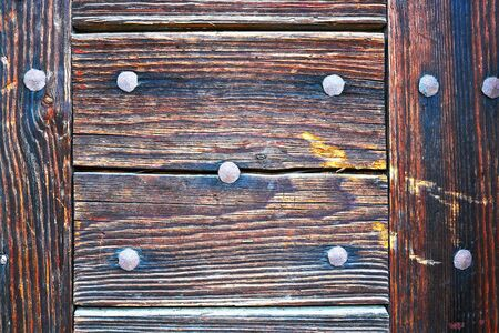details of a wooden door surface, planks mounted with rivets 스톡 콘텐츠