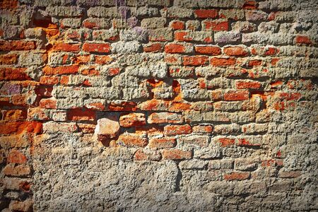 grungy damaged old red brick wall with broken plaster layer