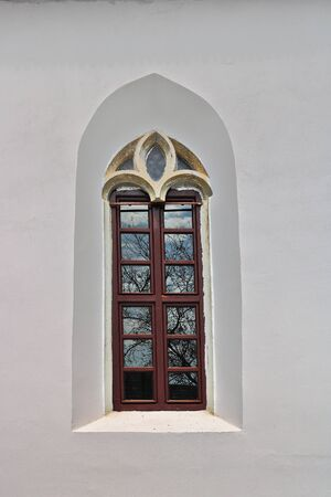 window on exteriorfacade of old gothic church with white painted walls
