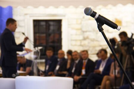 Investment Forum: microphone on the background of a businessman who speaks to the audience on stage. Stok Fotoğraf