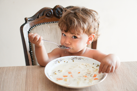 Small child sitting at table eating soup like a grown-up Stock Photo