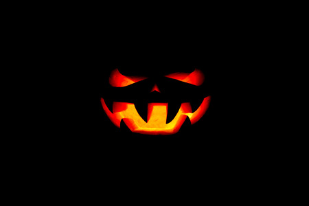 very scary Halloween pumpkin isolated on black background with illumination from within Stock Photo