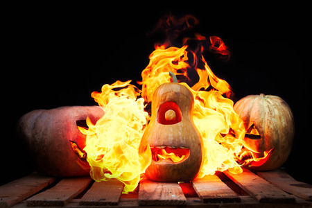 spew: Two Halloween pumpkins on the boards against each other spew flames fire on the third pumpkin on a black background