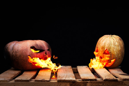 spew: Two Halloween pumpkins on the boards against each other spew flames fire on a black background