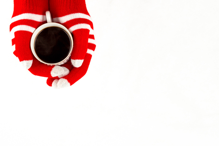 Christmas card, gloves on hands holding cup of cofee isolated on a white background with space for text