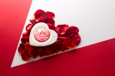 wallpaper International Women s Day: Candle heart on the heart of rose petals corner red white background with space for text