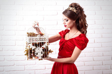 Elegant woman in a long red dress holding a bird cage with flowers on a background of a white brick wall Stock Photo