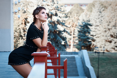 beautiful young girl with a beautiful make-up, in a short black dress, stands leaning on a railing sexy