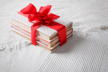Gift books beautifully wrapped and bandaged with a red ribbon bow on a white coverlet