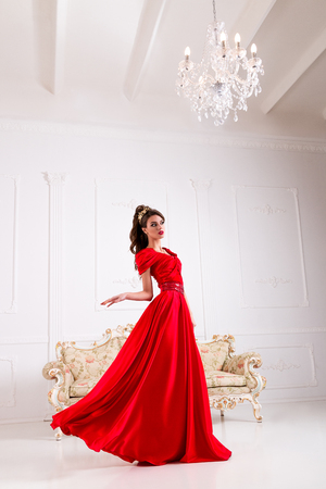 red sofa: Elegant woman in a long red dress is standing in a white room, dress flashing swirl flying Stock Photo