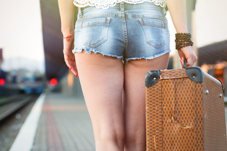 retro woman: Female legs, in sexy shorts in shoes with an old suitcase on the station platform Stock Photo