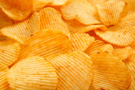 Background of golden wavy corrugated chips large slices with seasoning throughout the frame, appetizing food background