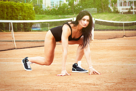 Beautiful young free sports sexy girl dressed in bodysuit, sneakers, with a smart ass and long legs, on the sports ground preparing to run Фото со стока