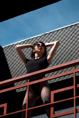 A beautiful young free sexy girl dressed in bodysuit in pantyhose and sunglasses stands at the red railing in shoes in the background of the grates, with a smart ass and long legs. Фото со стока